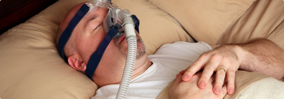 Man lying on bed with oxygen mask