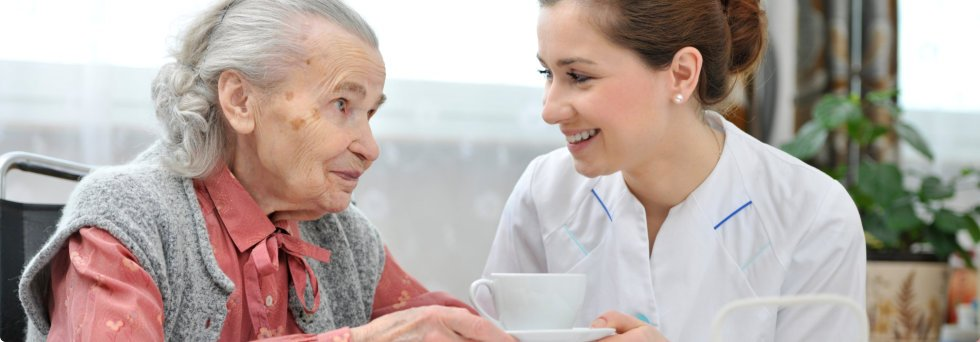 Caregiver serving a cup of tea to patient